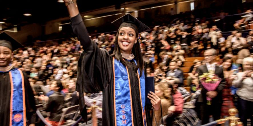 Student waving to crowd after graduating from Graziadio Business School