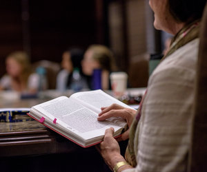 Woman reading Bible in class