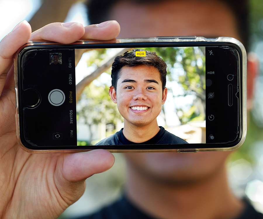 Man holding smart phone taking selfie photo
