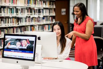 Two students working on computer in library