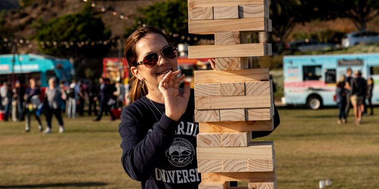 Female playing a game of Giant Jenga on Alumni Park