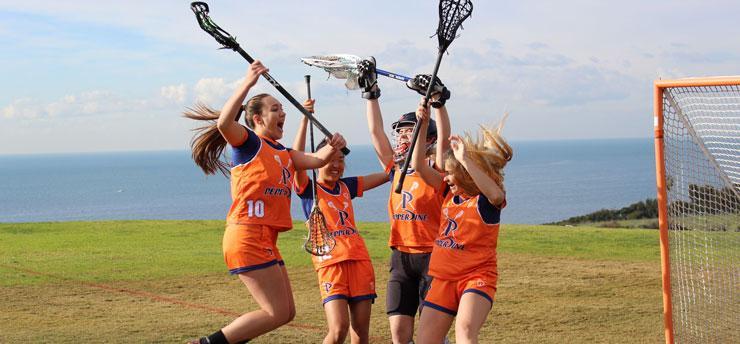 Pepperdine's Women's Lacrosse team members celebrating a goal