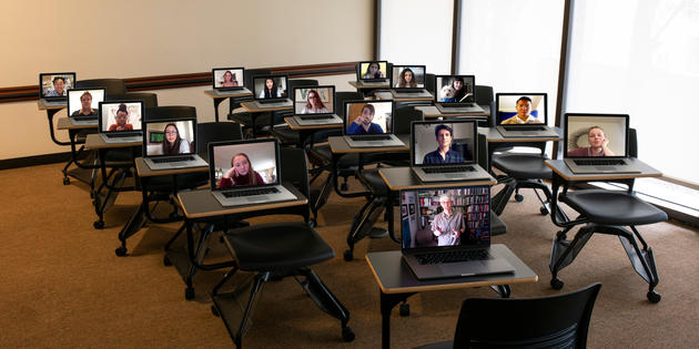 Opened laptops on a desks in a classroom with images of students on each screen